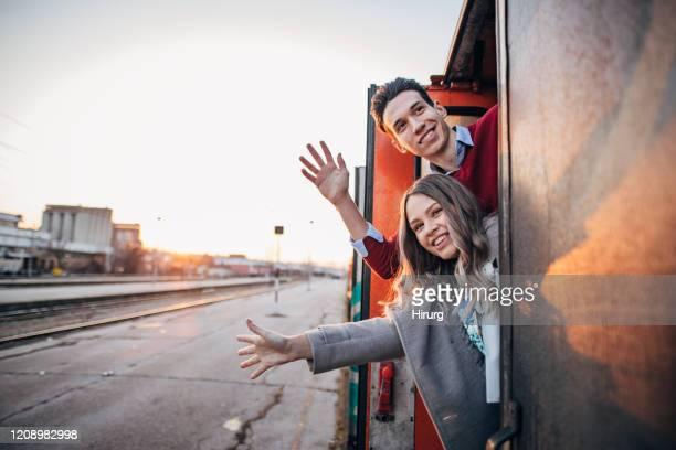 jong paar dat van de trein golft - zwaaien gebaren stockfoto's en -beelden