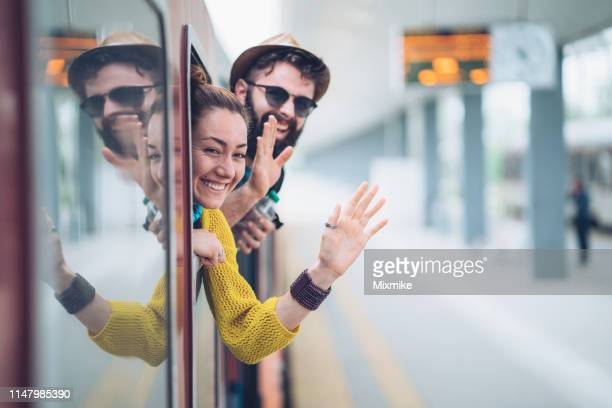 young couple waving from the train window - waving stock pictures, royalty-free photos & images