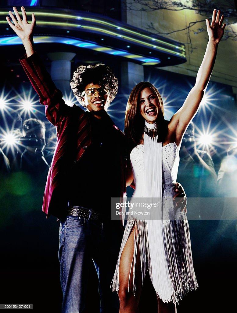 Young couple waving, smiling, crowd taking photos in background : Bildbanksbilder