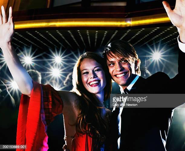young couple waving, smiling, crowd taking photos in background - première de film photos et images de collection