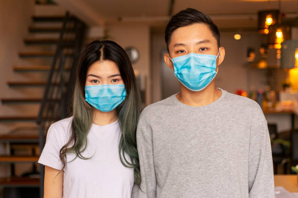 young couple wearing a protective face mask at home - asian people wearing face mask stock pictures, royalty-free photos & images