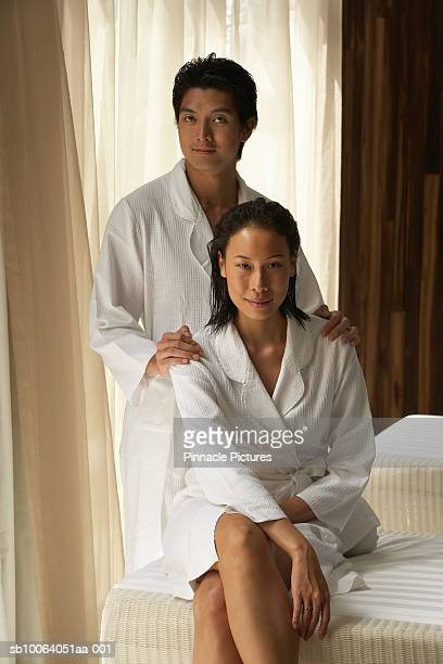 Young couple wearing bathrobes in bedroom, portrait