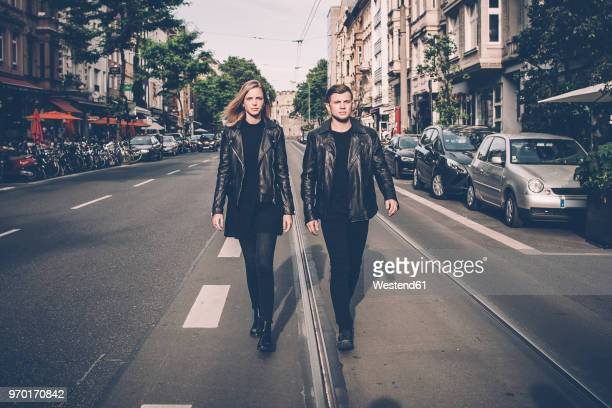 Young couple wearing black matching clothes walking side by side on the street