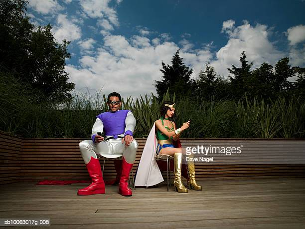 Young couple wearing costumes of fairy and superhero using mobile phones outdoors