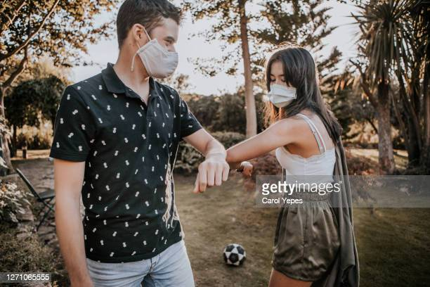 young couple wearing disposable face masks meeting in outdoors.. elbow bump - human limb stock pictures, royalty-free photos & images