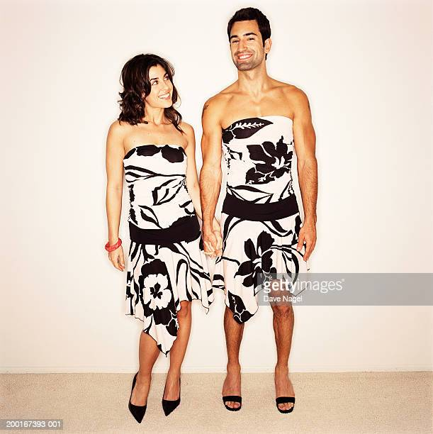 young couple wearing dresses, holding hands, portrait - transvestite stock photos and pictures