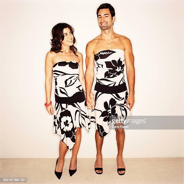 young couple wearing dresses, holding hands, portrait - crossdresser photos et images de collection