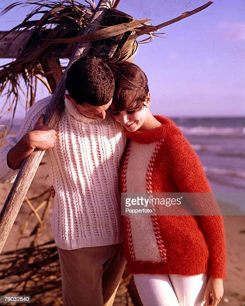 1964 A young couple wearing fashionable knitwear embrace as they walk on the beach The man is wearing a white woollen angora sweater and the woman a...
