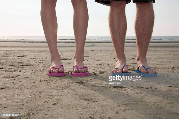 A young couple wearing flip-flops at the beach, low section