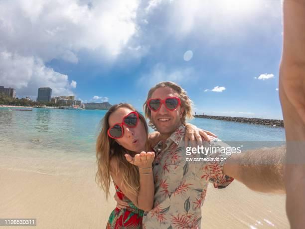 ワイキキのビーチで selfie 写真を撮るハート型の赤いサングラスを身に着けている若いカップル