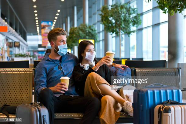 young couple wearing n95 face masks waiting in airport area - vacations stock pictures, royalty-free photos & images