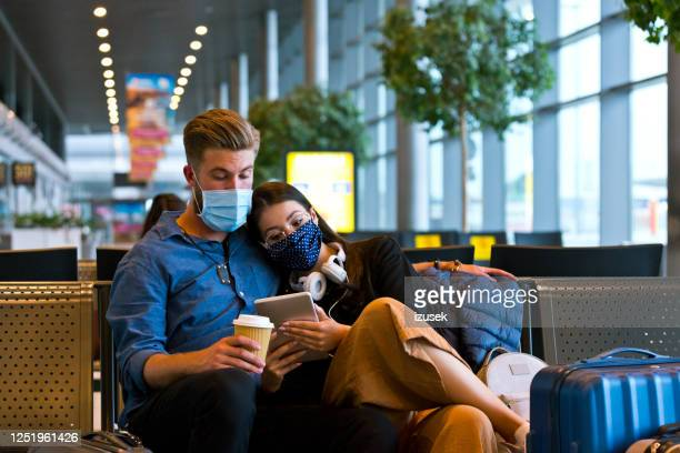 young couple wearing n95 face masks waiting in airport area - airport stock pictures, royalty-free photos & images