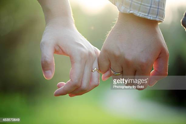 Young couple wearing rings hand in hand