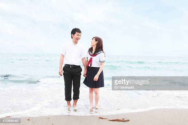 young couple wearing school uniform standing on sandy beach - ブレザー ストックフォトと画像