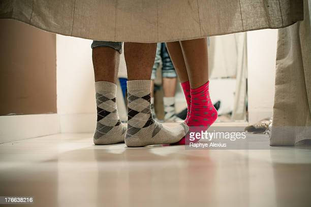 Young couple wearing socks in changing room, low section