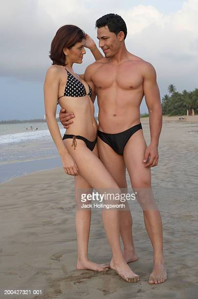 young couple wearing swimwear and standing on the beach - man wearing speedo stock photos and pictures