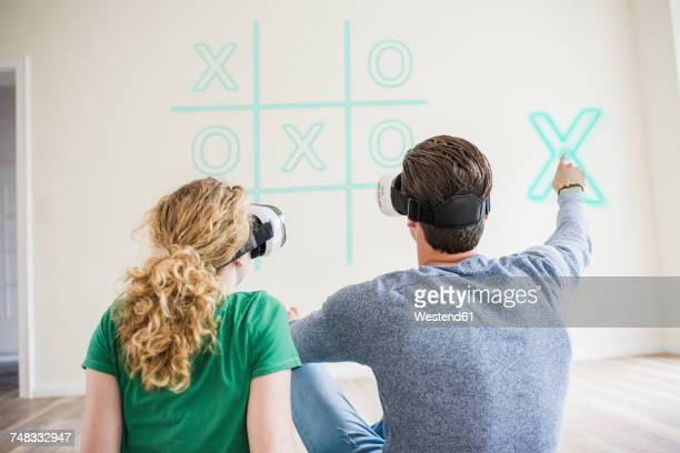 Young couple wearing VR glasses playing virtual tic tac toe