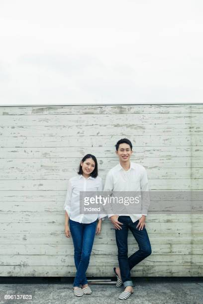 young couple wearing white shirt and jeans, smiling - 白いシャツ ストックフォトと画像