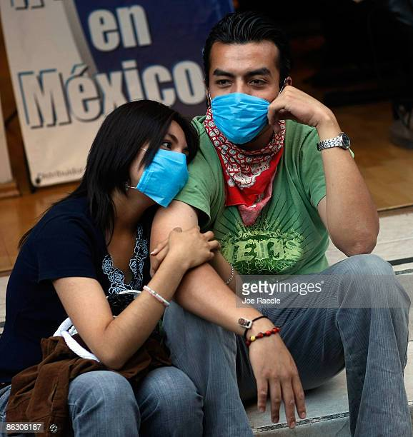 A young couple wears surgical masks to avoid swine flu contamination after the government has advised that nonessential government employees stay...
