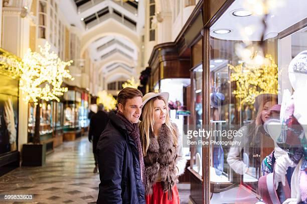 Young couple window shopping in Burlington Arcade at xmas, London, UK