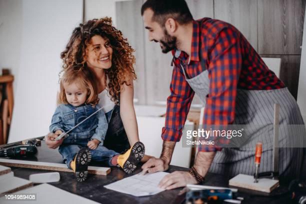 junges paar mit einem baby girl in einer werkstatt - kunsthandwerkliches erzeugnis stock-fotos und bilder
