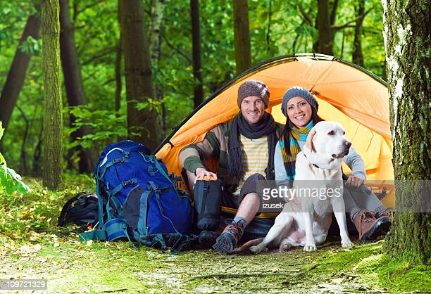 young couple with a dog camping - izusek stock pictures, royalty-free photos & images