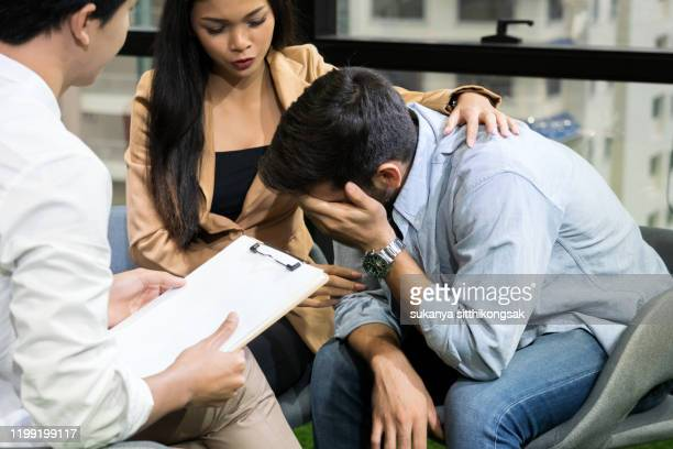 young couple with a problem to consult a psychologist. psychologist, counselor, therapist, psychiatrist or relationship consultant giving advice - 和解 ストックフォトと画像