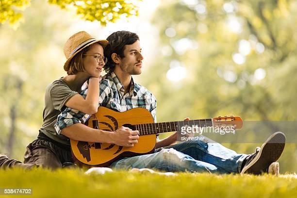 Casal Jovem com guitarra acústica relaxante no parque.
