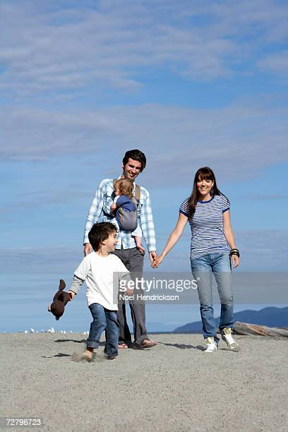 young couple with baby (6-9 months) and son (3-4 years) walking on beach - 25 29 years stock pictures, royalty-free photos & images
