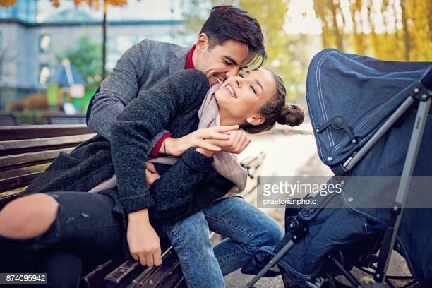 Jong (echt) paar met baby wandelwagen is knuffelen op de Bank in het park