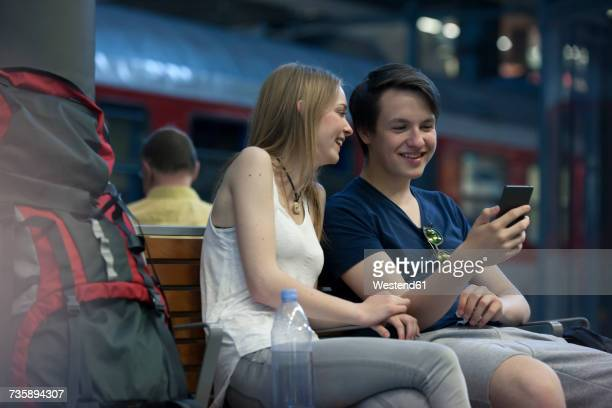 Young couple with backpacks sitting at rail station using smartphone