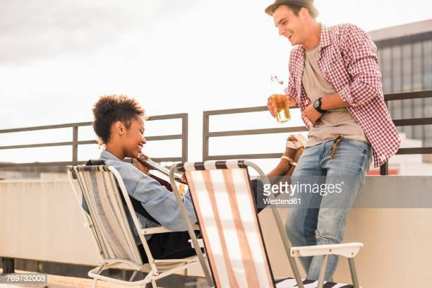 Young couple with beer and guitar on a rooftop party