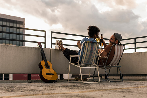Young couple with beer and guitar sitting on rooftop - gettyimageskorea