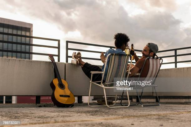 young couple with beer and guitar sitting on rooftop - spaß stock-fotos und bilder