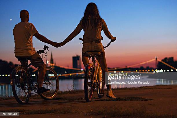 Young couple with bicycle at night, holding hands, Osijek, Croatia