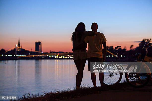 Young couple with bicycle at night, looking at city, Osijek, Croatia