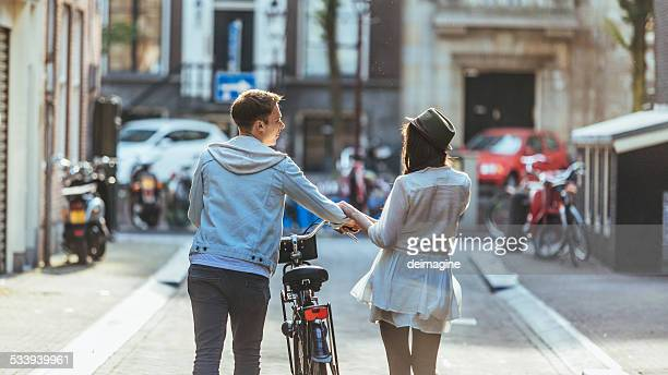 Young couple with bicycle through the city streets