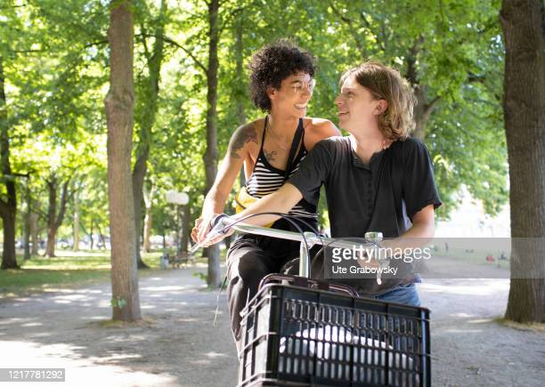 Young couple with bicycle walking under trees on May 29, 2020 in Bonn, Germany.