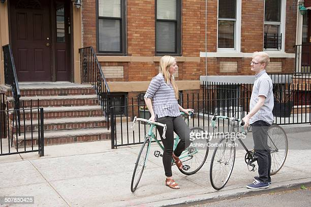 young couple with bicycles chatting on street - queens new york city stock pictures, royalty-free photos & images