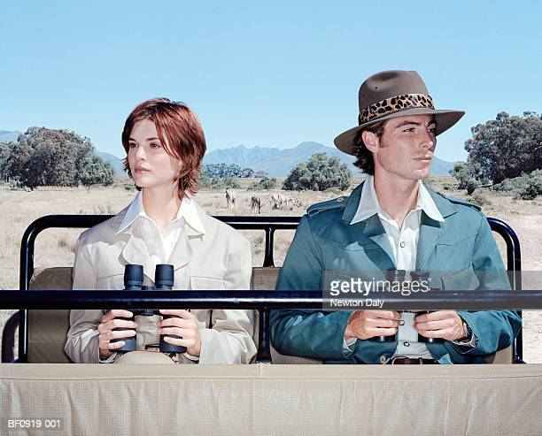 Young couple with binoculars side by side in open top vehicle