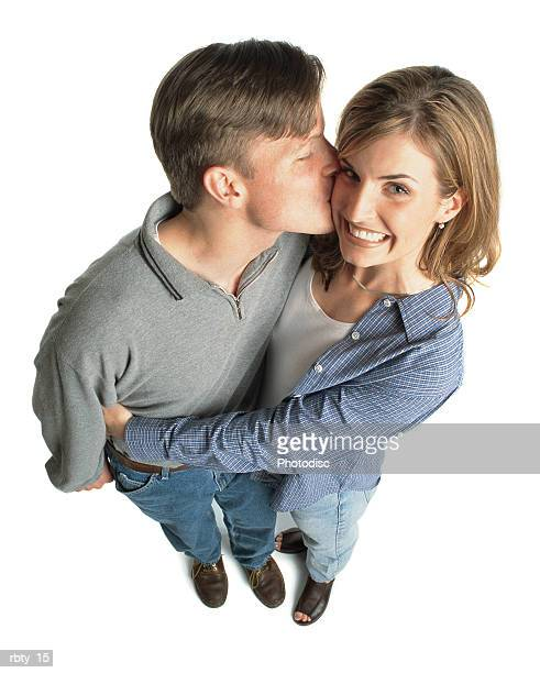 young couple with brown hair with the boy kissing the girl on the cheek and she is excited and smiles