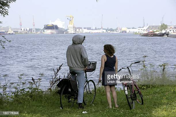 NETHERLANDS AMSTERDAM Young couple with bycicles in front of the backdrop of the Amsterdam harbour
