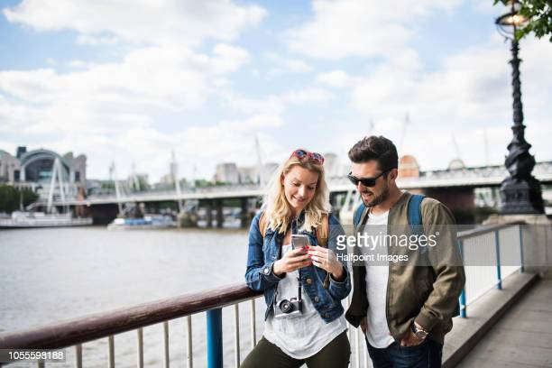 A young couple with camera standing by the river in a city, using smartphone.