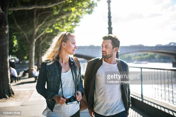 a young couple with camera walking by the river, talking. - fashionable stock pictures, royalty-free photos & images