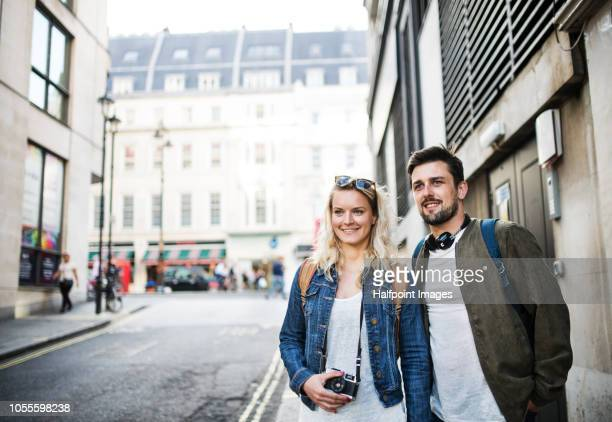 A young couple with camera walking on a street in a city, talking.