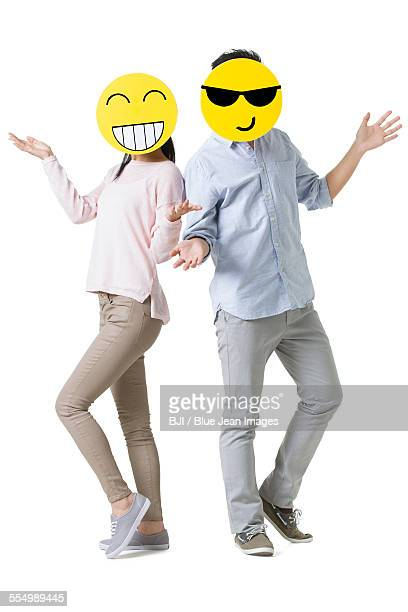 young couple with cartoon emoticon faces in front of their faces - smiley face stock pictures, royalty-free photos & images