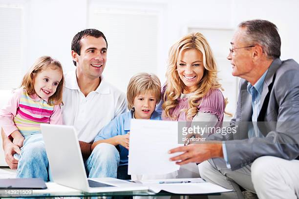 Young couple with children talking to financial advisor.
