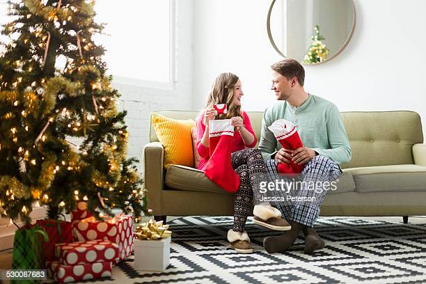 young couple with christmas stockings on sofa - men wearing stockings stock pictures, royalty-free photos & images