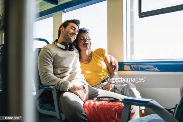 young couple with closed eyes relaxing in a train - bahnreisender stock-fotos und bilder