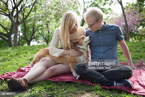 Young couple with corgi dog sitting in park